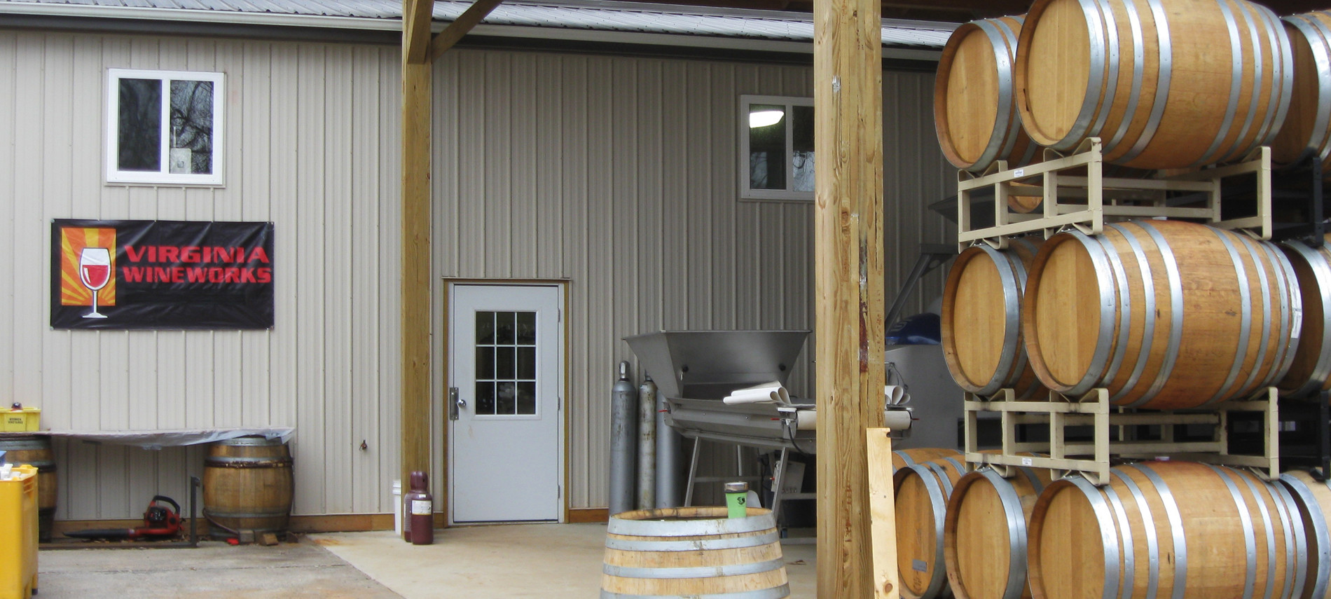 Exterior view of winery, brown barrels stacked in rack